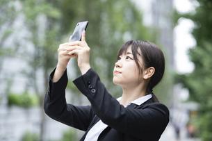スマートフォンで撮影するスーツ姿の若い女性の写真素材 [FYI04899785]