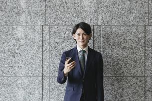 スマートフォンを持つ若い男性・IoTとビジネスのイメージの写真素材 [FYI04901200]