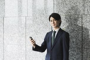 スマートフォンを持つ若い男性・IoTとビジネスのイメージの写真素材 [FYI04901201]