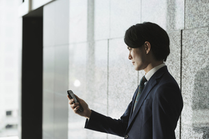 スマートフォンを持つ若い男性・IoTとビジネスのイメージ(逆光・横顔・シルエット)の写真素材 [FYI04901202]