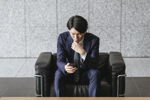スマートフォンを注視する若い男性・ソファに座る男性の写真素材 [FYI04901207]