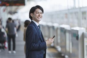 駅のホームでスマートフォンを持つ若い男性・通勤とIoTのイメージの写真素材 [FYI04901213]