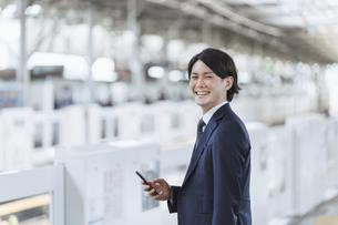駅のホームでスマートフォンを持つ若い男性・通勤とIoTのイメージの写真素材 [FYI04901217]