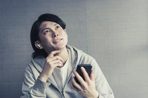 ワイヤレスイヤホンで好きな音楽を聞く若い男性の写真素材 [FYI04901247]