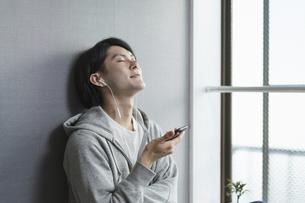 月額の音楽を楽しむ若い男性・サブスクやユーチューブ動画を見るの写真素材 [FYI04901262]