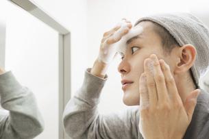 洗面台でフェイスケアをする若い男性・化粧水と洗顔の写真素材 [FYI04901264]