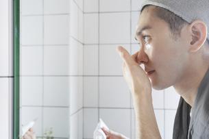 洗面台でフェイスケアをする若い男性・化粧水と洗顔の写真素材 [FYI04901270]