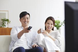 リビングでテレビを観ながらくつろぐ女性と男性の写真素材 [FYI04902140]