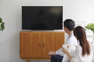 リビングでテレビを観ながらくつろぐ女性と男性の写真素材 [FYI04902146]