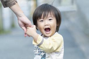 母親と手を繋いだまま振り返る男の子の写真素材 [FYI04902378]