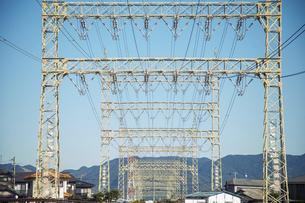 高圧電線と鉄塔と青空と街並みの写真素材 [FYI04902444]
