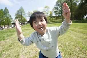 キャンディーを食べながら嬉しそうに踊る男の子の写真素材 [FYI04902475]