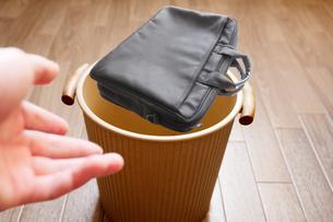 使い古したカバンをゴミ箱へ投げ捨てるの写真素材 [FYI04902532]