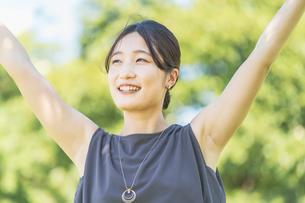 緑の中でリラックスする若い女性の写真素材 [FYI04902925]