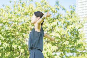 緑の中でリラックスする若い女性の写真素材 [FYI04902930]