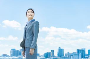 都心と青空を背景に立つ若いビジネスウーマンの写真素材 [FYI04902967]