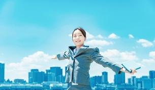 都心と青空を背景に立つ若いビジネスウーマンの写真素材 [FYI04902973]