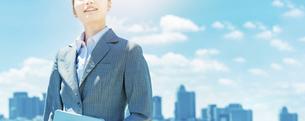 都心と青空を背景に立つ若いビジネスウーマンの写真素材 [FYI04902975]