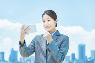 スマートフォンの画面を熱心に見つめるビジネスウーマンの写真素材 [FYI04902979]