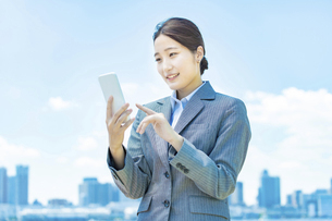 スマートフォンを操作するビジネスウーマンの写真素材 [FYI04902980]