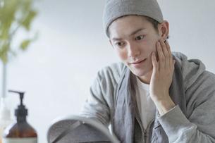 若い男性のフェイシャルケアのイメージ・家でのフェイスケアの写真素材 [FYI04903107]