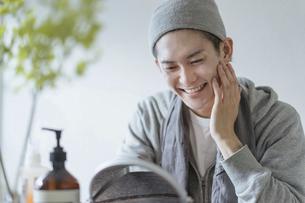 若い男性のフェイシャルケアのイメージ・家でのフェイスケアの写真素材 [FYI04903110]