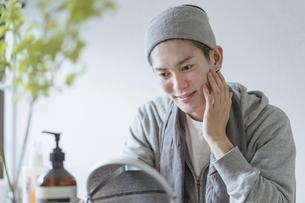 若い男性のフェイシャルケアのイメージ・家でのフェイスケアの写真素材 [FYI04903112]