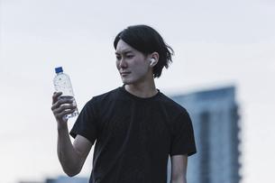 夕方のランニング・水を手に持つ若い男性の写真素材 [FYI04903134]