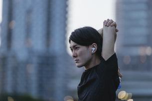 音楽を聞きながらジョギングの準備をする若い男性の写真素材 [FYI04903135]