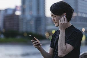 屋外で音楽を聞きながらランニングの準備をする若い男性の写真素材 [FYI04903141]
