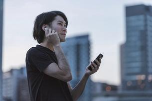 屋外で音楽を聞きながらランニングの準備をする若い男性の写真素材 [FYI04903145]