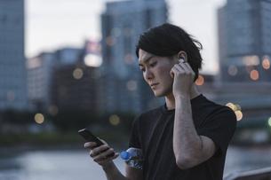 屋外で音楽を聞きながらランニングの準備をする若い男性の写真素材 [FYI04903151]