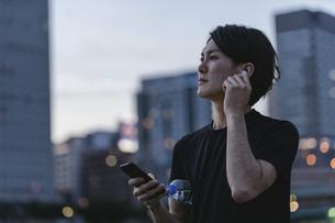 屋外で音楽を聞きながらランニングの準備をする若い男性の写真素材 [FYI04903152]