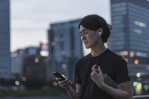 屋外で音楽を聞きながらランニングの準備をする若い男性の写真素材 [FYI04903153]