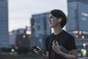屋外で音楽を聞きながらランニングの準備をする若い男性の写真素材 [FYI04903154]