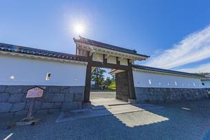 小田原城址公園 二の丸正面に構える馬出門から覗く天守閣と輝く太陽の写真素材 [FYI04904509]