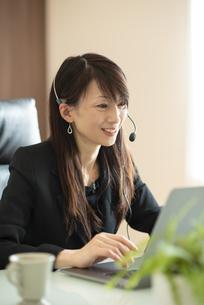 デスクで顧客対応をするビジネスウーマンの写真素材 [FYI04904919]