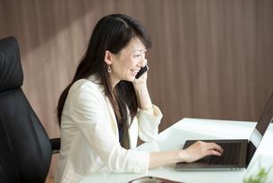 デスクで顧客対応をするビジネスウーマンの写真素材 [FYI04904956]