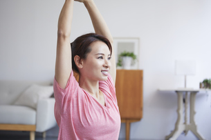 自宅でトレーニングをする笑顔の女性の写真素材 [FYI04905193]