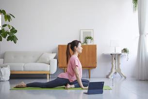 タブレット端末を見ながら自宅でトレーニングをする笑顔の女性の写真素材 [FYI04905194]