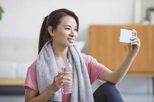 スマホを見ながら自宅でトレーニングをする笑顔の女性の写真素材 [FYI04905195]