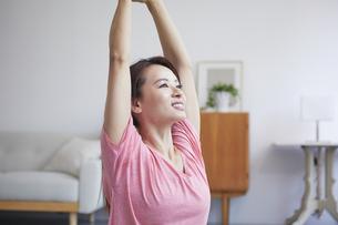 自宅でトレーニングをする笑顔の女性の写真素材 [FYI04905196]