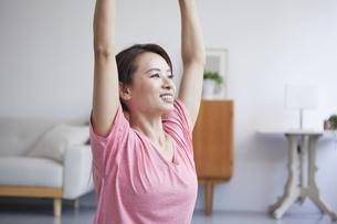 自宅でトレーニングをする笑顔の女性の写真素材 [FYI04905199]