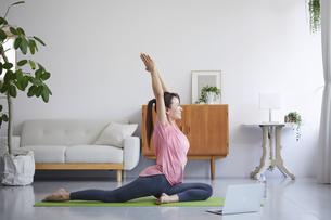 ノートパソコンを見ながら自宅でトレーニングをする笑顔の女性の写真素材 [FYI04905202]