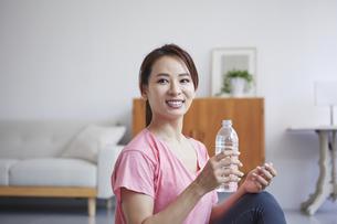 自宅でトレーニングをする笑顔の女性の写真素材 [FYI04905203]