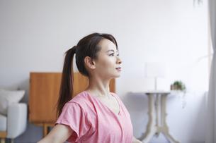 自宅でトレーニングをする笑顔の女性の写真素材 [FYI04905204]