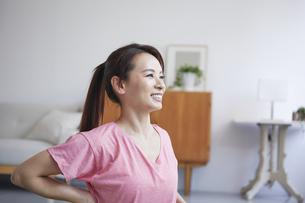 自宅でトレーニングをする笑顔の女性の写真素材 [FYI04905206]
