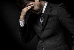 頭を抱えて悩む男性の写真素材 [FYI04905226]