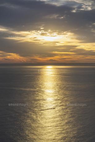 太陽の照らした道を横断する漁船の写真素材 [FYI04906351]
