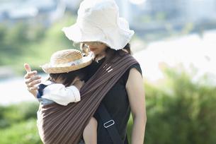 スリングを使って幼児を抱く母親の写真素材 [FYI04906697]